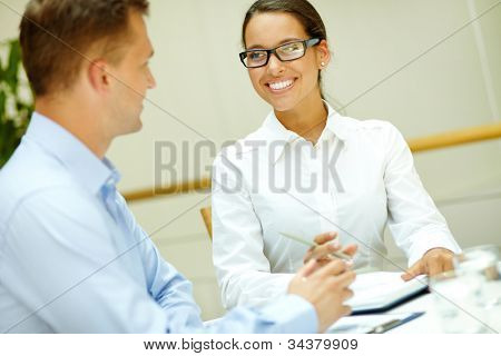 Image of a beautiful office worker smiling to her male colleague