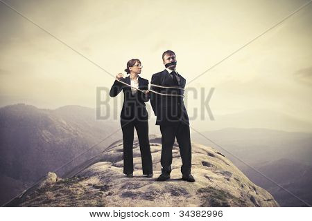 Businesswoman tying tight a businessman on a mountain peak