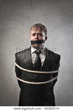 Sad businessman tied and muffled