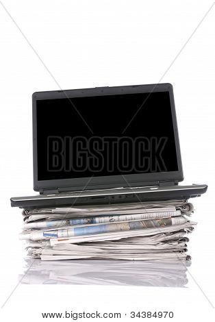 Laptop On Stacking Newspaper