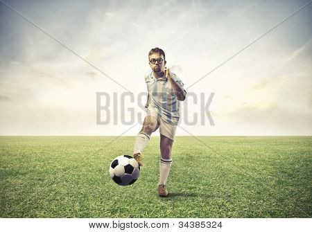 Soccer player shooting a football on a meadow
