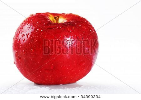 Bright Red Apple With Water Drops Over White