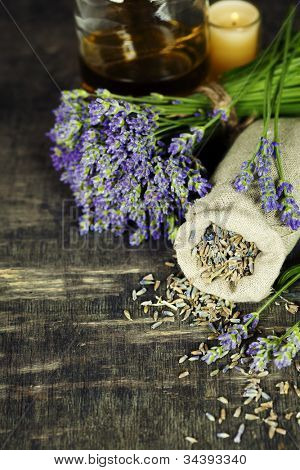 Fresh and dried lavender flowers, essential oil, soap and Herbal massage balls over wooden surface