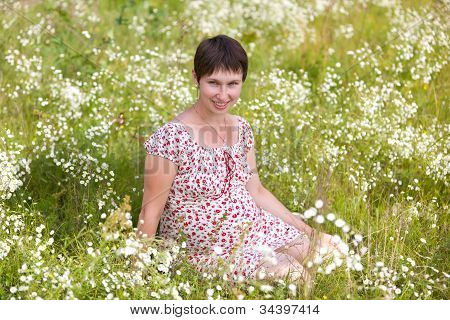 Cheerful Pregnant Woman Sitting In Chamomile