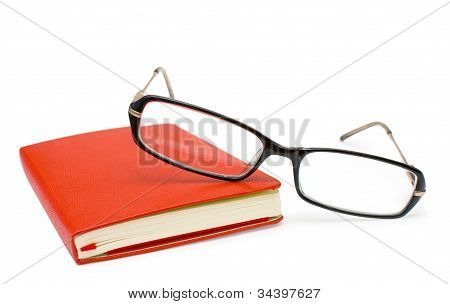 Red Closed Notepad  And Glasses Isolated On White