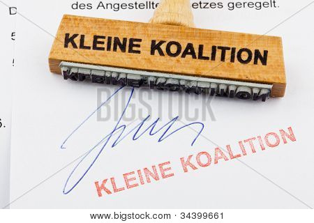 a stamp made of wood lying on a document. german inscription: small coalition