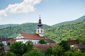 Landscape Of Small Village Under The Hill. Landscape With Small Church In Village. Morning Landscape poster