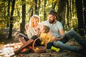 Basket With Picnic Meal And Toys For The Kid. Happy Family Of Three Lying In The Grass In Autumn. Th poster