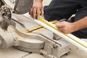 stock photo of baseboard  - Contractor Measuring for Circular Saw Cutting of New Baseboard Renovation - JPG