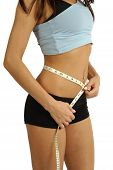 image of tape-measure  - A tanned slim young woman measuring her waistline - JPG
