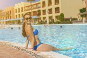 Young Beautiful Woman In Bikini Sitting On Edge Of Swimming Pool, Outdoors. Beautiful Girl With Rela poster