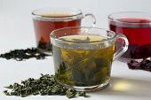 Green Hot Tea With Dry Leaves On A White Table. Three Glass Cups With Black, Red And Green Tea On A  poster