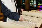 picture of torah  - Boy in Synagogue pointing at Hebrew on Torah - JPG