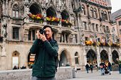 Young Asian Traveling Backpacker In City Centre In Europe. Man Taking Photos In Marienplatz Square,  poster
