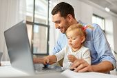 multi-tasking, freelance and fatherhood concept - working father with baby daughter and laptop compu poster