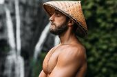 Portrait Of A Sports Guy In An Asian Conical Hat. Portrait Of A Man In Profile. Portrait Of A Bearde poster