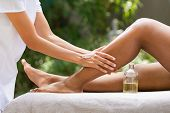 Closeup of masseuse hands giving essential oil massage to woman in outdoor spa resort. African ameri poster