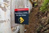 Danger Hazardous Cliffs Do Not Enter With Person Falling Sign Next To A Concrete Wall poster