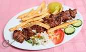 picture of souvlaki  - A lamb souvlaki or kebab on the skewer served with french fried potato chips rice and vegetables at a taverna - JPG