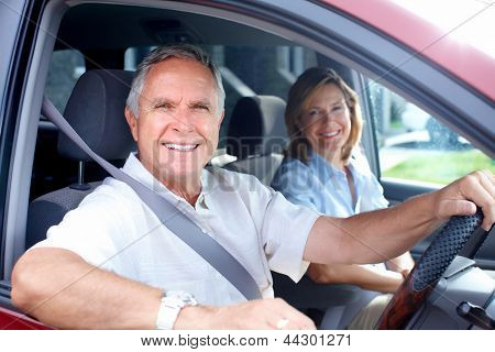Happy senior couple in the car. Transportation.