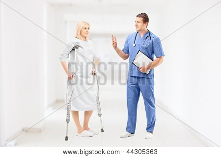 Female patient in gown with crutches and medical doctor during a conversation in clinical corridor