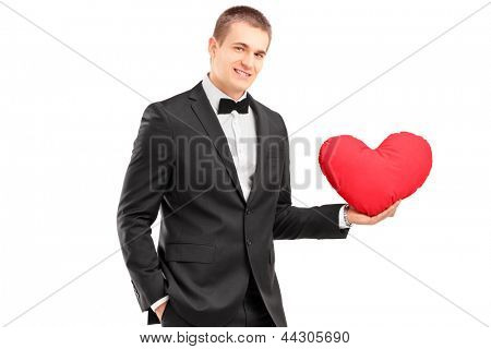 A young man wearing black suit and holding a red heart isolated on white background