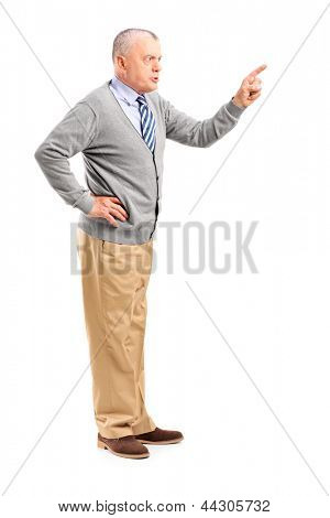 Full length portrait of an angry mature man pointing with finger and threatening isolated on white background