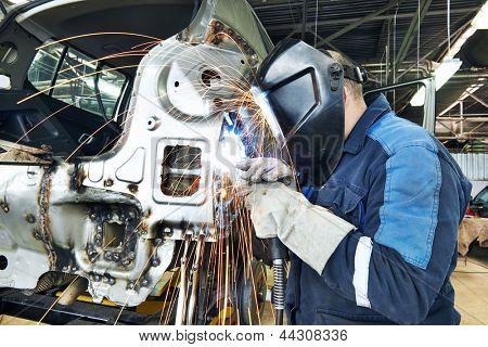 trabajador reparador profesional en la industria automotriz soldadura metal carrocería con chispas
