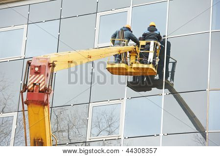 Tho builders worker installing glass windows on facade of business building