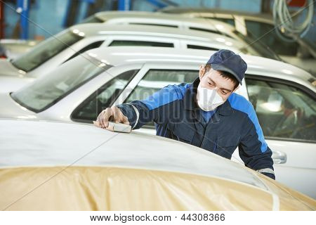 professional repairman worker in automotive industry sanding metal caer roof before painting at bodywork