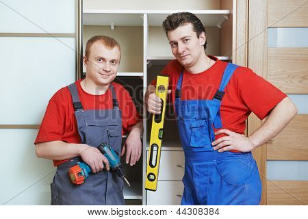 Portrait of happy carpenter worker team in front of home built-in cupboard