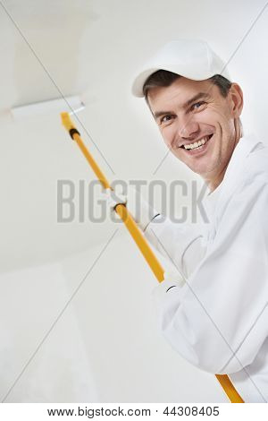 Portrait of one smiling male house painter worker with painting roller