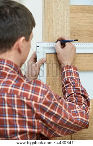Male handyman carpenter at interior wood door lock installation with angle