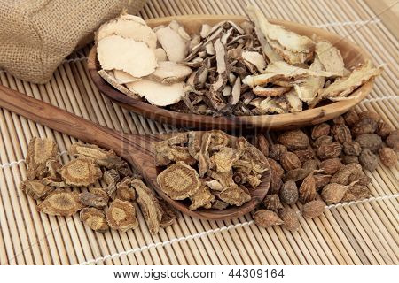 Chinese herbal medicine selection in a wooden spoon, bowl and loose over bamboo mat.