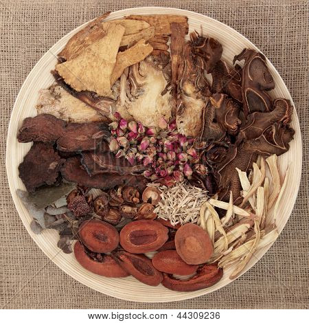 Traditional chinese herbal medicine selection on a round wooden bowl over hessian background.