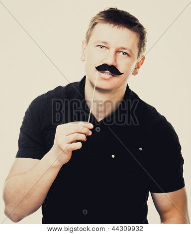 Young man with fake mustache. picture over light background