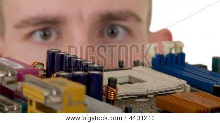 Man Examines An Electronic Circuit