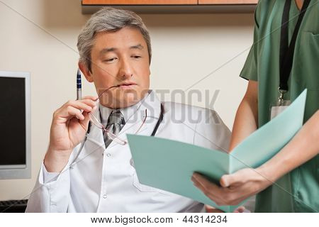 Midsection of male technician showing patient's file to mature doctor