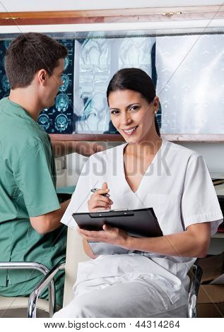 Portrait of female medical technician holding clipboard while colleague working in background