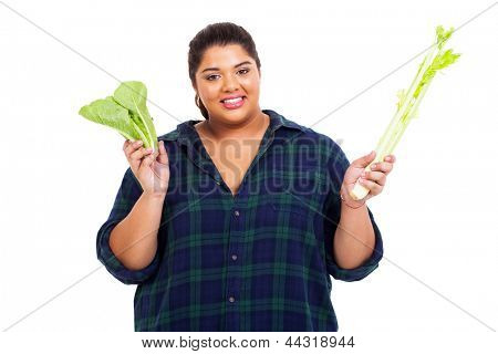 happy overweight woman holding green vegetables on white background