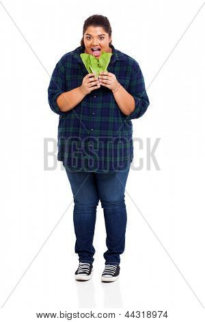 portrait of plus size beautiful woman eating lettuce over white background