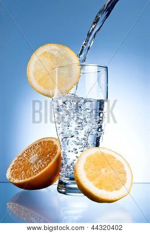 Mineral Water Glass With Lemon And Orange On A Blue Background