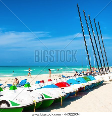 VARADERO,CUBA-APRIL 7:Boats for rent and tourists enjoying the beach April 7,2013 in Varadero.With a growth of 4.5% in 2012,tourism has consolidated as a primary source of income for Cuba