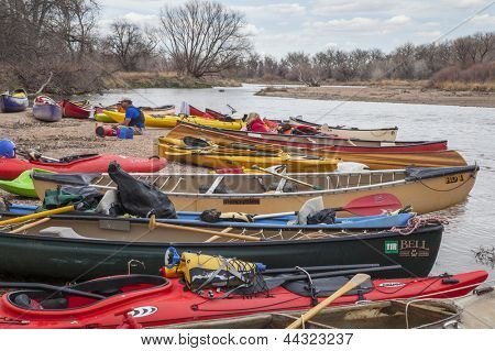 SOUTH PLATTE RIVER, EVANS, COLORADO - APRIL 6: Kayaks and canoes on a river shore during Annual All Club Paddle on April 6, 2013. It is a popular season opening paddling trip in northern Colorado.
