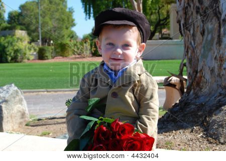 Little Boy Waiting On A Bench With A Dosens Of Red Roses