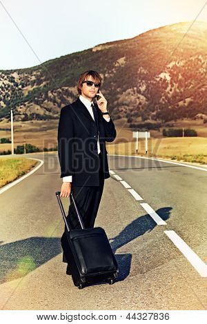 Handsome business man standing on a highway with his suitcase and calling by phone.
