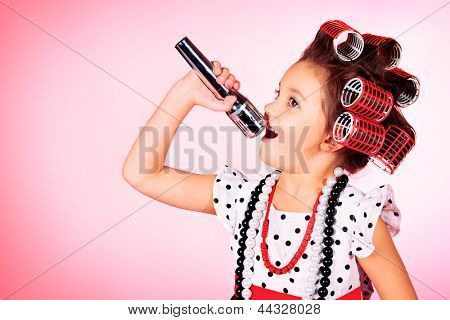 Portrait of a cute little pin-up girl singing with a microphone. Pink background.
