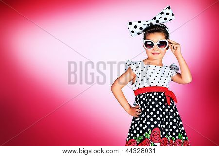 Portrait of a cute little pin-up girl in a beautiful dress and big bow.
