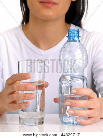 Young woman holding potable water bottle and glass.