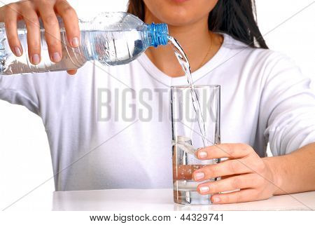 Young woman pouring potable water on a glass.